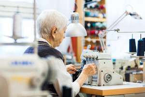 Mature clothier working by sewing-machine