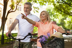 Mature couple with bicycles in park
