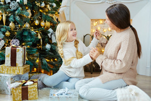 Mature female having fun with her granddaughter by xmas tree