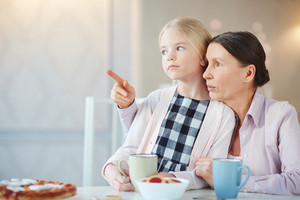 Mature female pointing forwards while showing something to her granddaughter