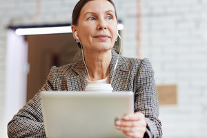 Mature female with touchpad listening to music at break