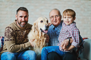 Mature man, young man, little boy and pet looking at camera