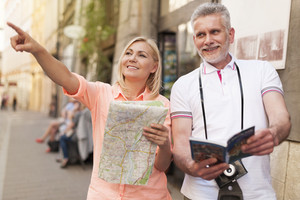 Mature tourist sightseeing city with map and guidebook