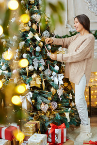 Mature woman decorating Christmas tree at home