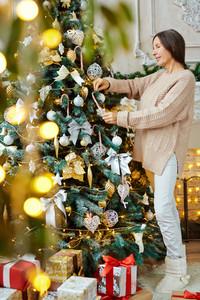 Mature woman decorating Christmas tree at home