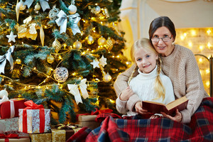 Mature woman embracing her granddaughter during relax by xmas tree