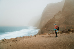 Men hiker with backpack on the scenic coastal road. The route leads along huge volcanic rock cliffs above roaring ocean and joins the towns of Cruzinha and Ponta do Sol. Santo Antao. Cape Verde