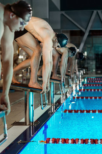 Men standing on starting blocks preparing to begin swimming race