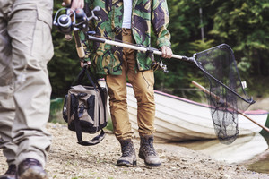 Men walking and carrying fishing tackle