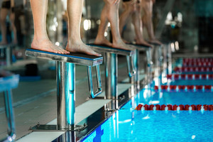 Men's feet standing on starting blocks preparing to begin swimming race