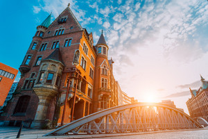 Metal arch bridge and old red bricks building in the Speicherstadt warehouse district of Hamburg HafenCity with sunburst light during sunset golden hour and white clouds against blue sky above