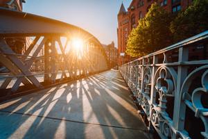 Metal arch bridge in the Speicherstadt of Hamburg with sunburst light during sunset golden hour
