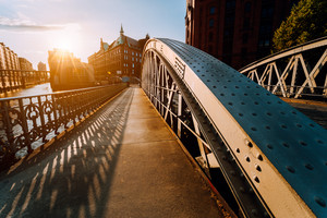 Metal arch bridge with rivets in the Speicherstadt of Hamburg during sunset golden hour with sunburst in horizon