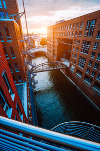 Metal staircase, bridge over canal and red brick buildings in the old warehouse district Speicherstadt in Hamburg in golden hour sunset light, Germany. View from above