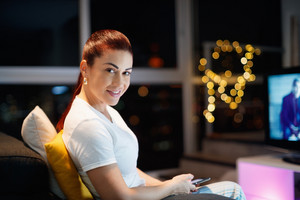 Mid adult woman sitting on sofa at night, chatting with mobile phone. 40 years old latin american woman sending message on social network with smartphone, smiling at camera