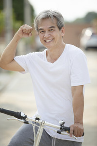 middle age asian man toothy smiling face happiness emotion exercise by riding bicycle in home village street
