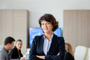 Middle aged business woman in conference room. Woman suit.