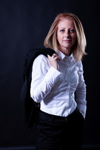 Middle aged business woman photoshoot in studio on blackground.