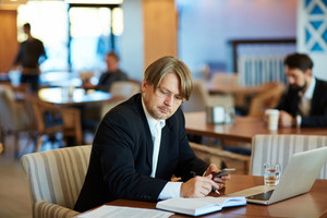 Middle-aged entrepreneur focused on work while sitting in spacious cafe, modern laptop, documents and notebook located on table