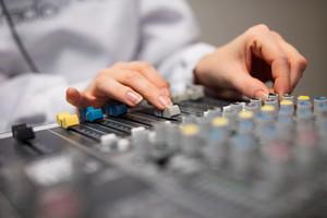 Midsection Of Radio Host's Hands Using Music Mixer In Studio