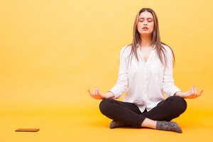 Millennial girl taking a break from her phone and practicing meditation over yellow background. Peaceful state of mind