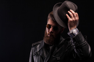 Misterious handsome bearded man with half of his face in the shadow while holding his hat over black background. Attractive man.