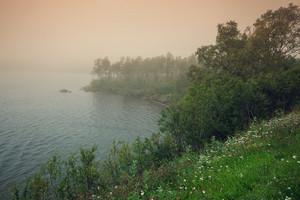 Misty morning over lake. Rural landscape.