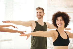 Mixed group of fitness people doing exercises indoors