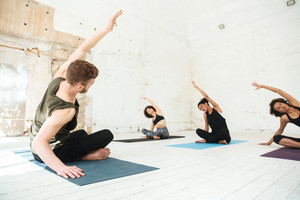 Mixed group of young people doing yoga class and using mats