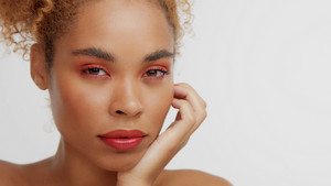 mixed race black blonde model with curly hair and red makeup touhes her cheek watching to the camera