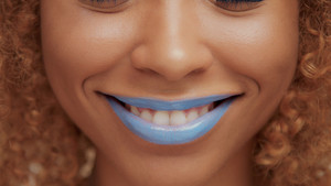 mixed race black blonde model with curly hair closeup of mouth painted with bright blue lipstick. Closeup smilie