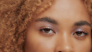 mixed race black blonde model with curly hair eyes closeup watching at camera. ideal skin