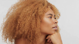 mixed race black blonde model with curly hair in profile turned to the right