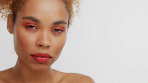 mixed race black blonde model with curly hair with red makeup calm watching to the camera