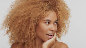 mixed race black blonde model with curly hair wondered model turned face to the right