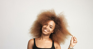 mixed race black woman with blonde curly hair in studio happy smiling