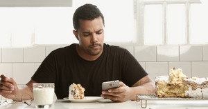 mixed race man in caffe has a breakfast with smartphone