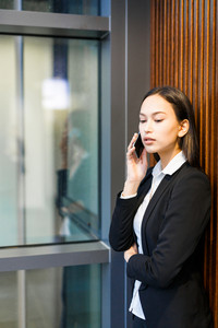 Mixed race young businesswoman answering on phone call while leaning to wall in office lobby, portrait shot