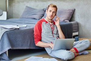 Mobile businessman in homewear sitting on the floor by his bed, networking and speaking by smartphone