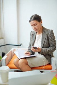 Mobile businesswoman making notes in notebook