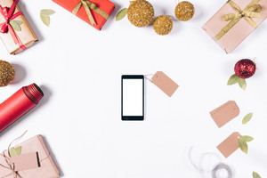 Mobile phone, boxes with gifts and Christmas decorations on a white table top view