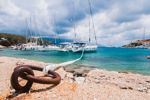 Mooring rope tied to rusty ring for rigging yachts in background. Wonderful view of port Fiskardo. Picturesque seascape of Ionian Sea. Outdoor scene of Kefalonia island, Greece, Europe
