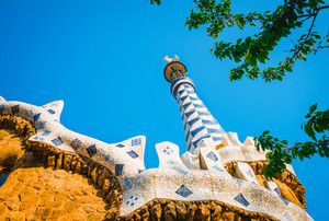 Mosaic tower and colorful roof decorations of Gingerbread House of Gaudi in Park Guell, Barcelona, Spain