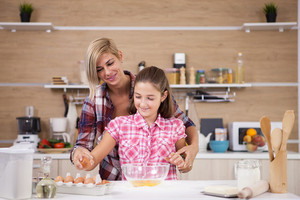 Mother and daughter cook together at home and having fun. Kid learning to cook