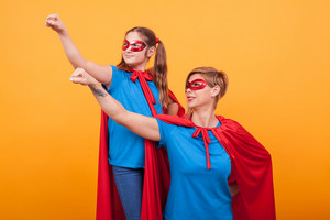 Mother and daughter dressed like heroins holding their fist in the air and looking away over yellow background. Happy childhood. Mom super powers.