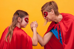 Mother and daughter dressed like superheroes playing arm wrestling over yellow background. Super mom. Super daughter. Red cape. Red mask. Parenting.