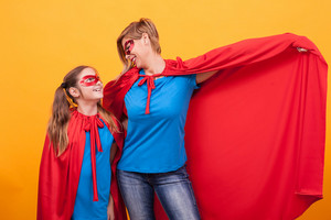 Mother and daughter dressed like superheros bonding over yellow background. Mother and daughter playing. Motherhood. Happy childhood.