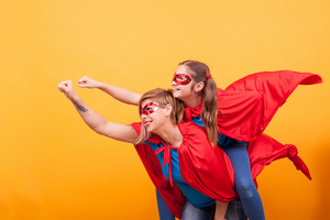 Mother and daughter dressed like superheros flying off save the world from villans. Red and blue costume. Playing together.