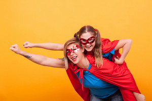 Mother and daughter dressed like superheros flying off to save the world from villans. Red and blue costume. Playing together.