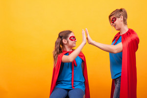 Mother and daughter dressed like superheros giving hi5 over yellow background. Red cape. red mask. Superhero costume.